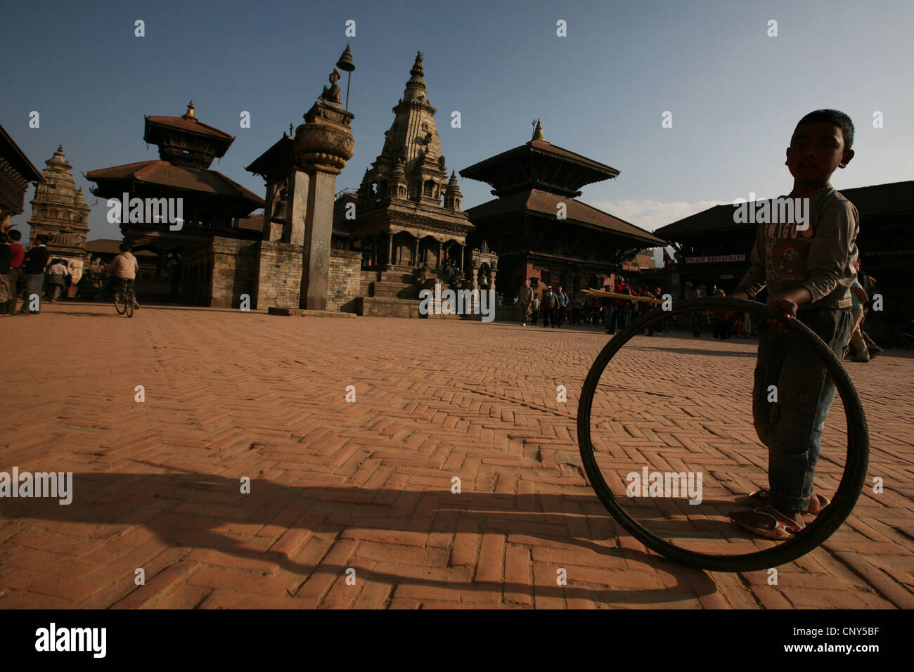 Nepalese boy plays with a pneumatic in Bhaktapur Durbar Square in Bhaktapur, Nepal. Stock Photo