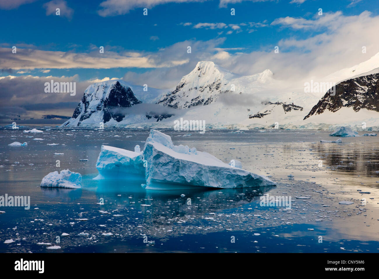 Icebergs drifting past snow covered mountains on the Gerlache Straight, Antarctic Peninsula, Antarctica. Summer - Stock Image