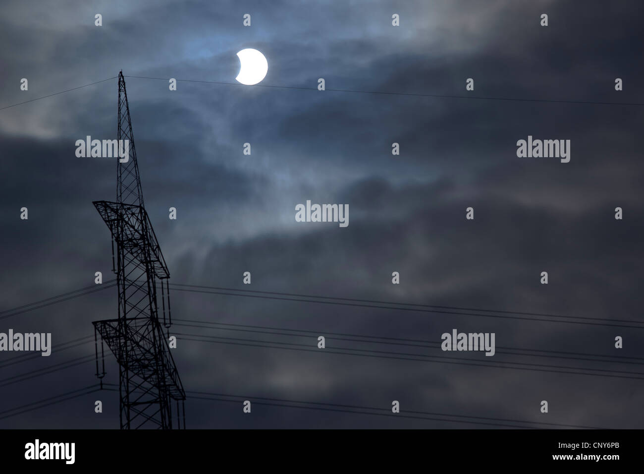 partial eclipse of the moon in a cloudy sky - Stock Image