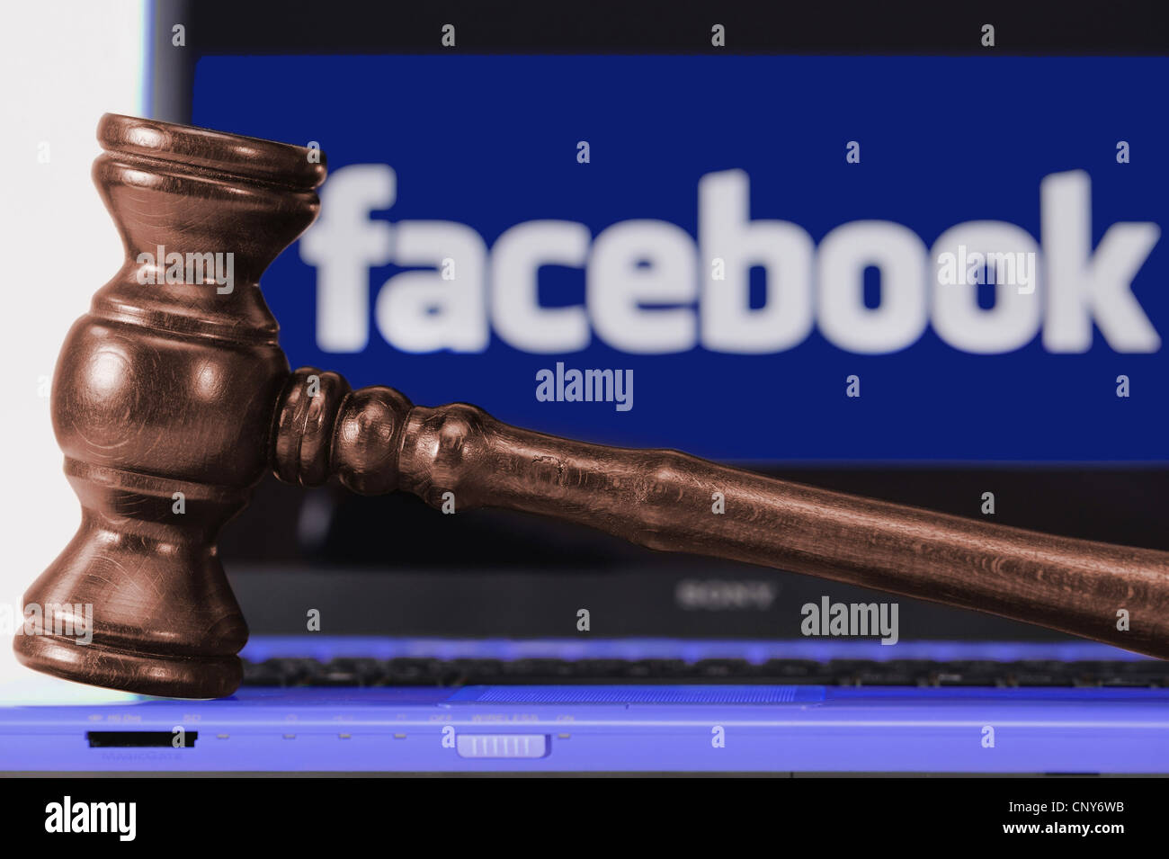 the Facebook logo under a magnifying glass symbolising the legally doubtful aspects of the platform - Stock Image