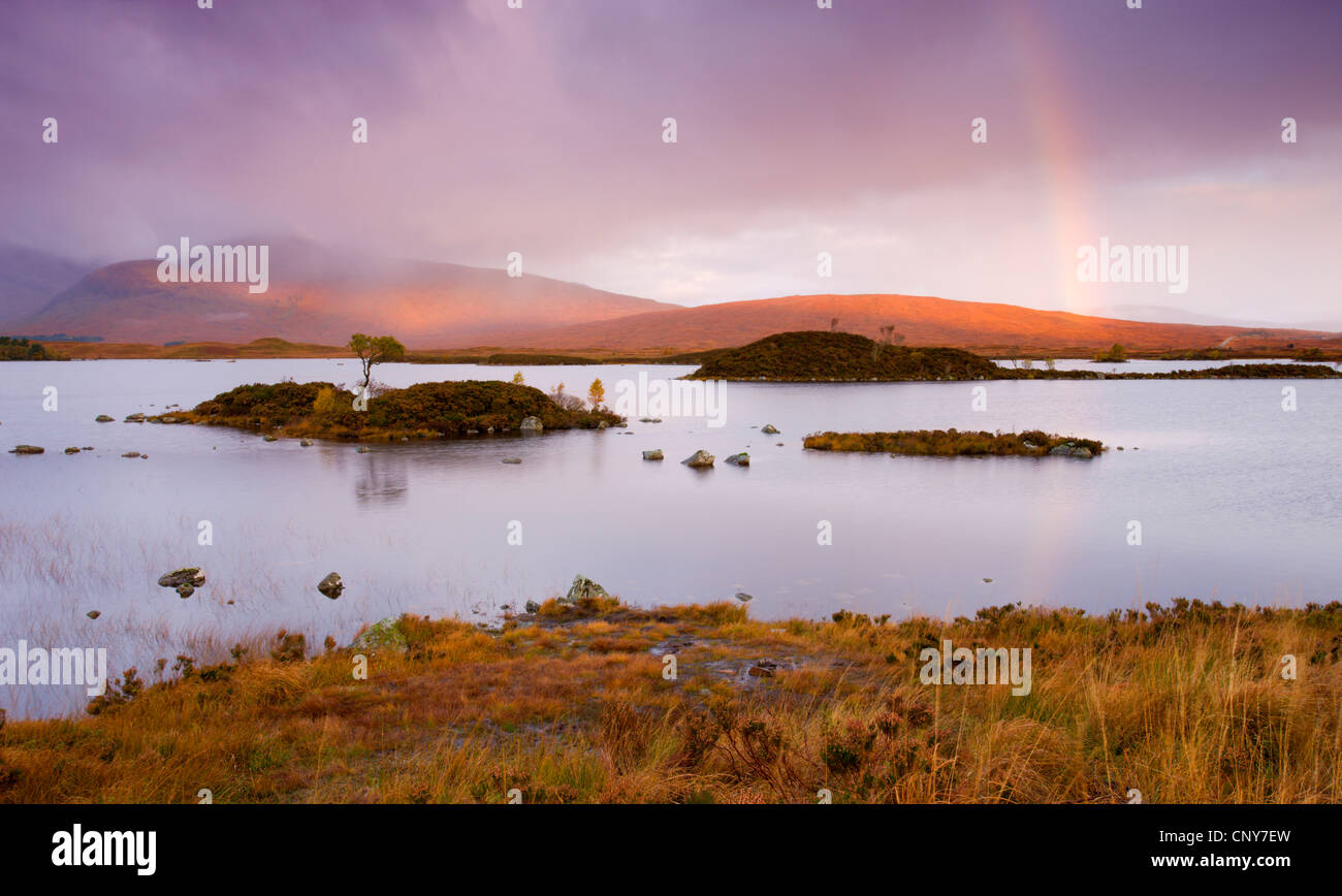 Rainbow in stormy skies over Lochan Na H-Achlaise on Rannoch Moor in Autumn, Highlands, Scotland - Stock Image