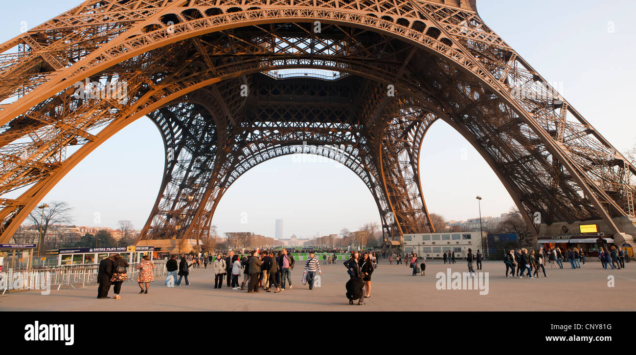 Visitors at the base of the Eiffel Tower give a sense of scale, Paris - Stock Image