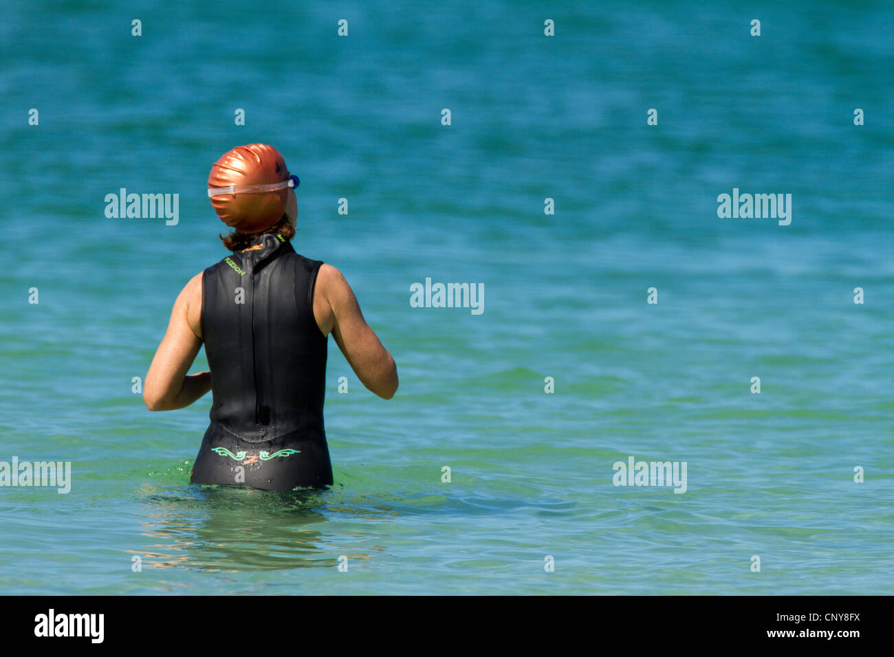 Female swimmer wearing a swimming cap and suit stands in the blue water of a  Atlantic Ocean - Gulf of Mexico - Stock Image