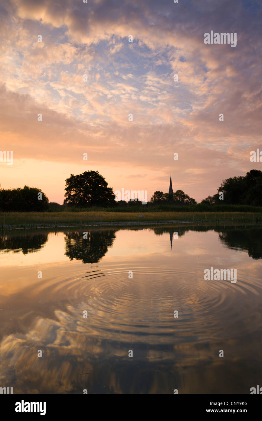 Salisbury Cathedral Spire and a beautiful dawn sky reflected in a rippled pond, Salisbury, Wiltshire, England. - Stock Image