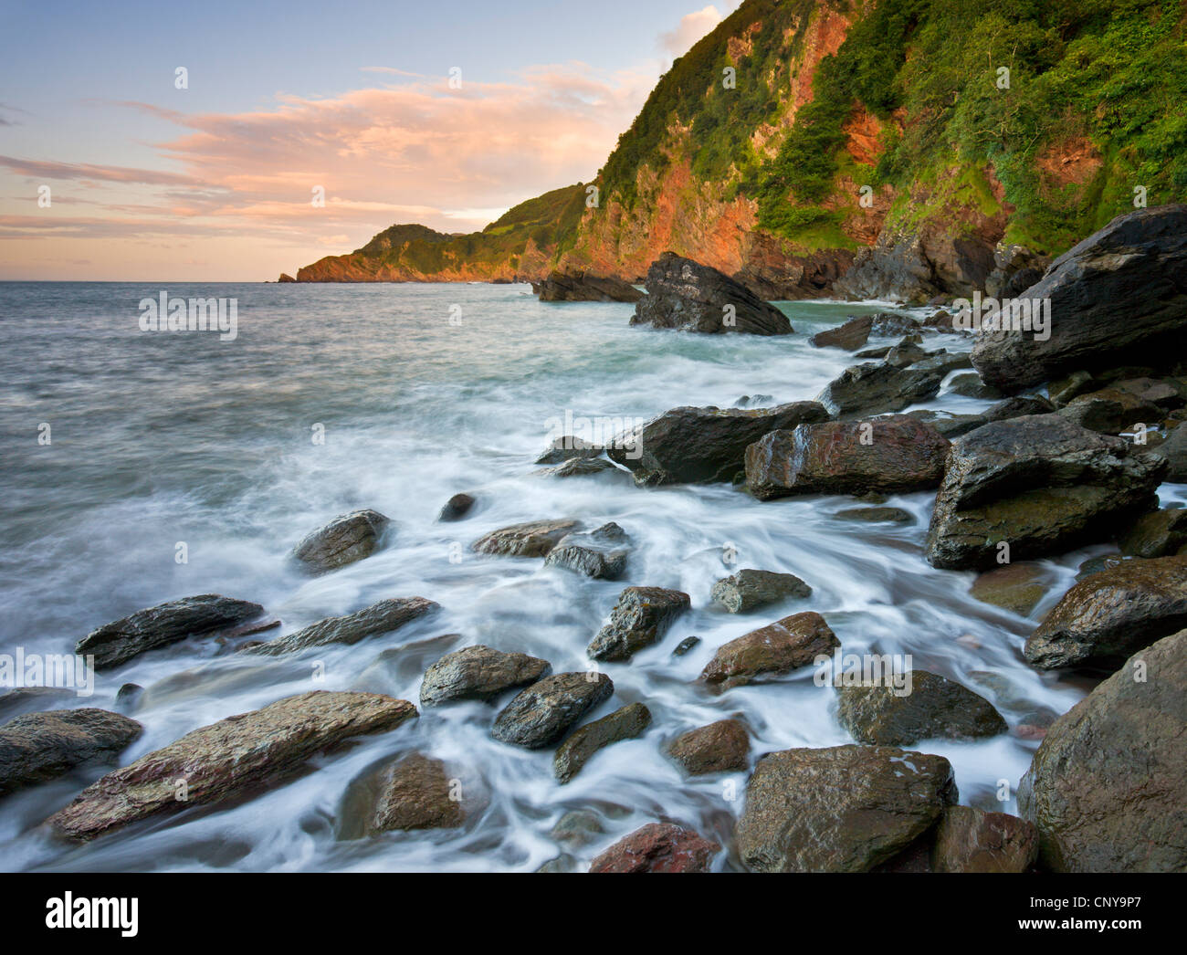 Waves crash around the rocky shores of Woody Bay at high tide, Exmoor National Park, Devon, England. Summer (August) - Stock Image