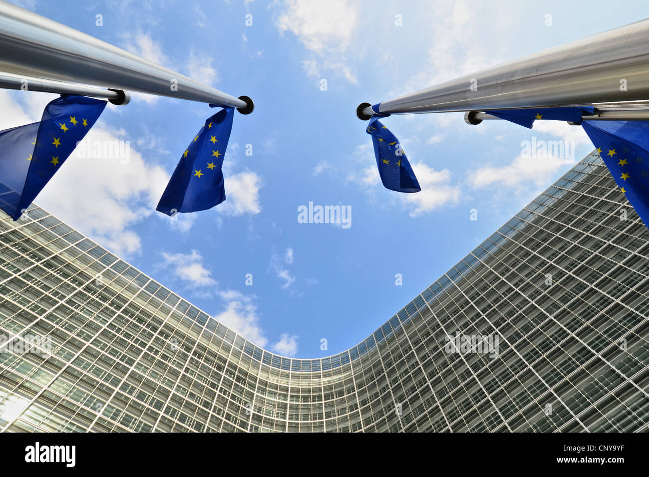 Flag poles and European Union flags flying outside the European Commission Berlaymont headquarters in Brussels, - Stock Image