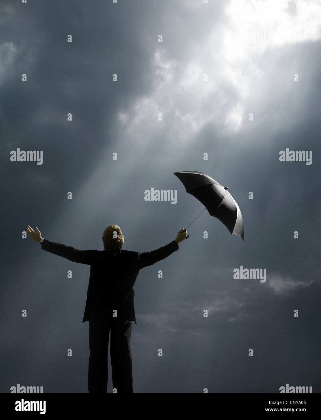 Man holding umbrella standing in sunlight rays - Stock Image