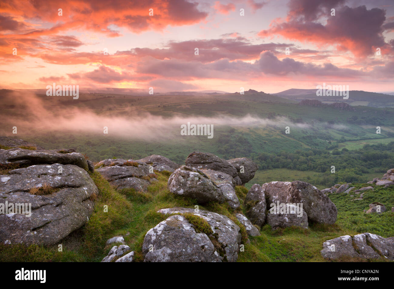 Dramatic sunset above a misty moorland near Hound Tor, Dartmoor National Park, Devon, England. Summer (July) 2010. - Stock Image