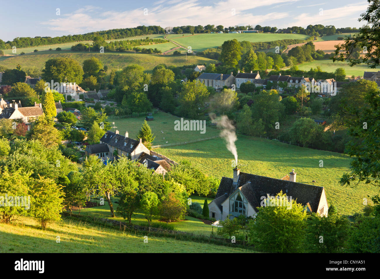 Cottages nestled into the valley in the picturesque Cotswolds village of Naunton, Gloucestershire, England. Summer - Stock Image