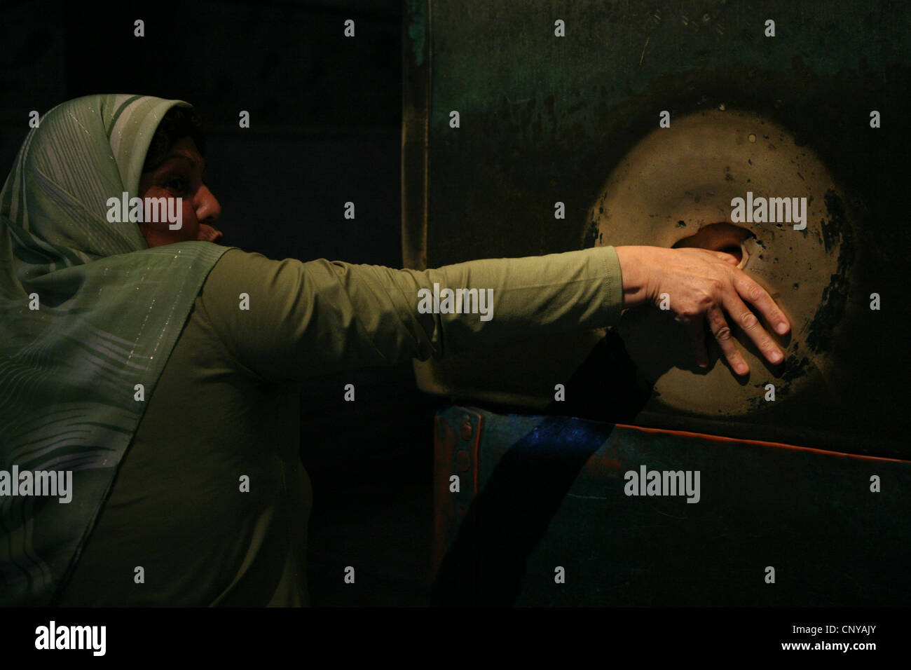 Turkish woman rotates her thumb in the hole in the Weeping Column in Hagia Sophia in Istanbul, Turkey. - Stock Image
