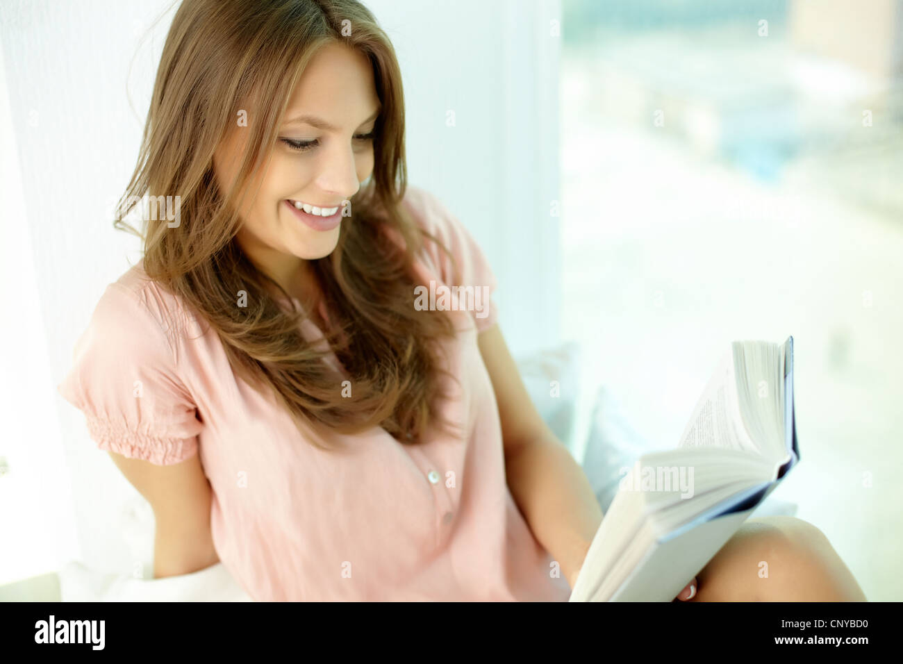 Girl being totally absorbed in an interesting book - Stock Image