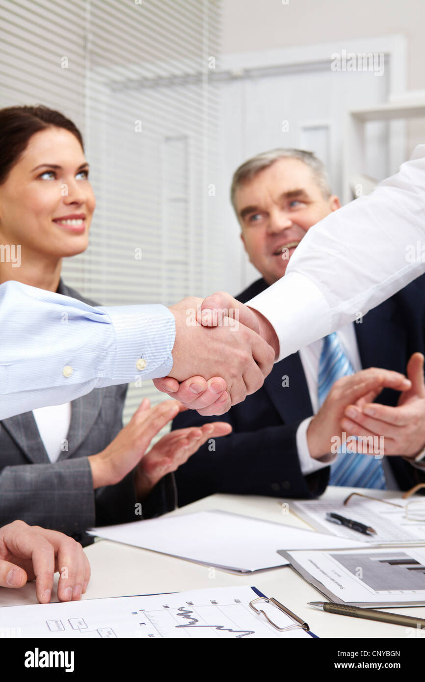 Businessmen shaking hands, their colleagues applauding cheerfully - Stock Image