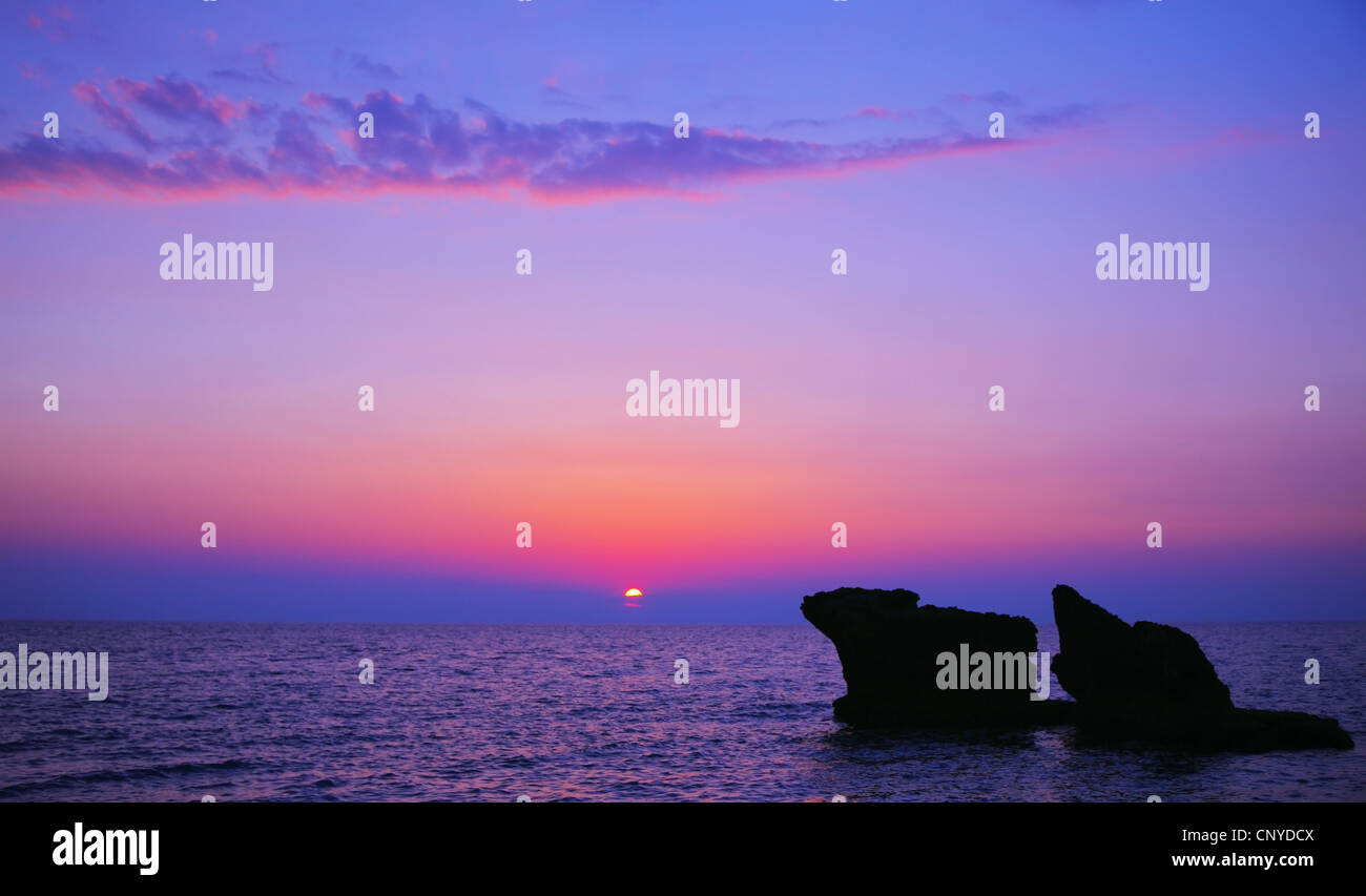 Beautiful purple sunset on the beach, seascape with calm ocean and rocks in the blue water - Stock Image