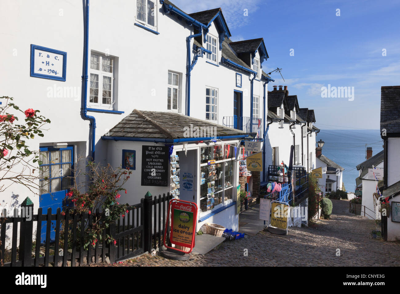 Local shop on steep narrow cobbled street in quaint picturesque village with view to the sea in Clovelly North Devon Stock Photo