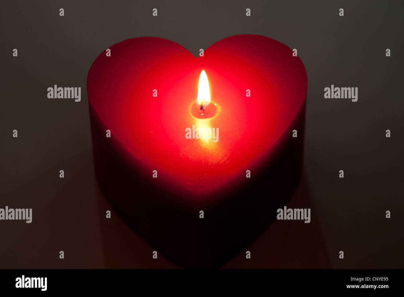 A red heart shaped candle, lit - Stock Image
