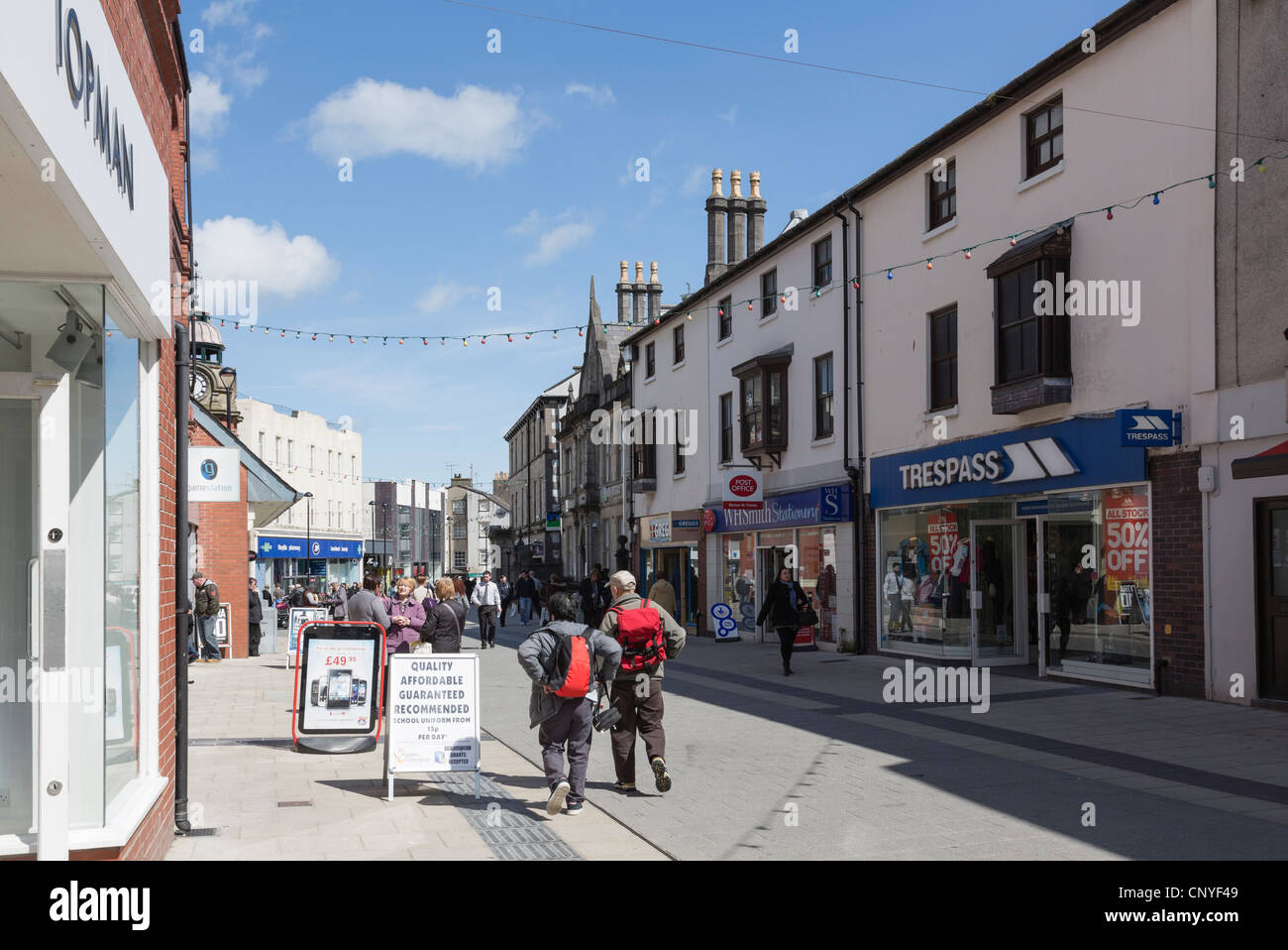 Street scene with people and shops in the city centre shopping precinct. High Street, Bangor, North Wales, UK, Britain. - Stock Image
