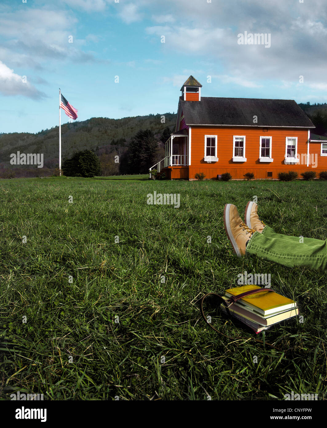 Person laying in Grass by Little Red Schoolhouse - Stock Image