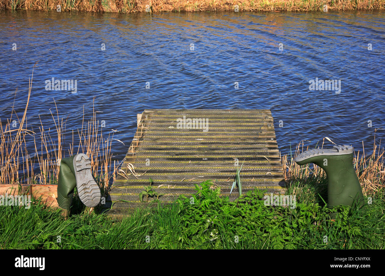 A pair of upturned water boots with staging on a river bank on the Norfolk Broads. - Stock Image