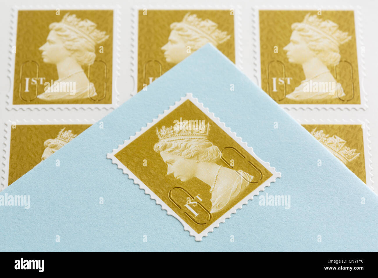 UK, Britain. Royal Mail first class postage stamps and an envelope with a stamp stuck on - Stock Image