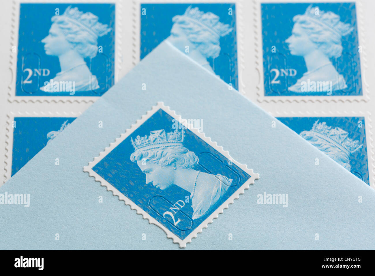 UK, Britain. Royal Mail second class postage stamps and an envelope with a stamp stuck on - Stock Image