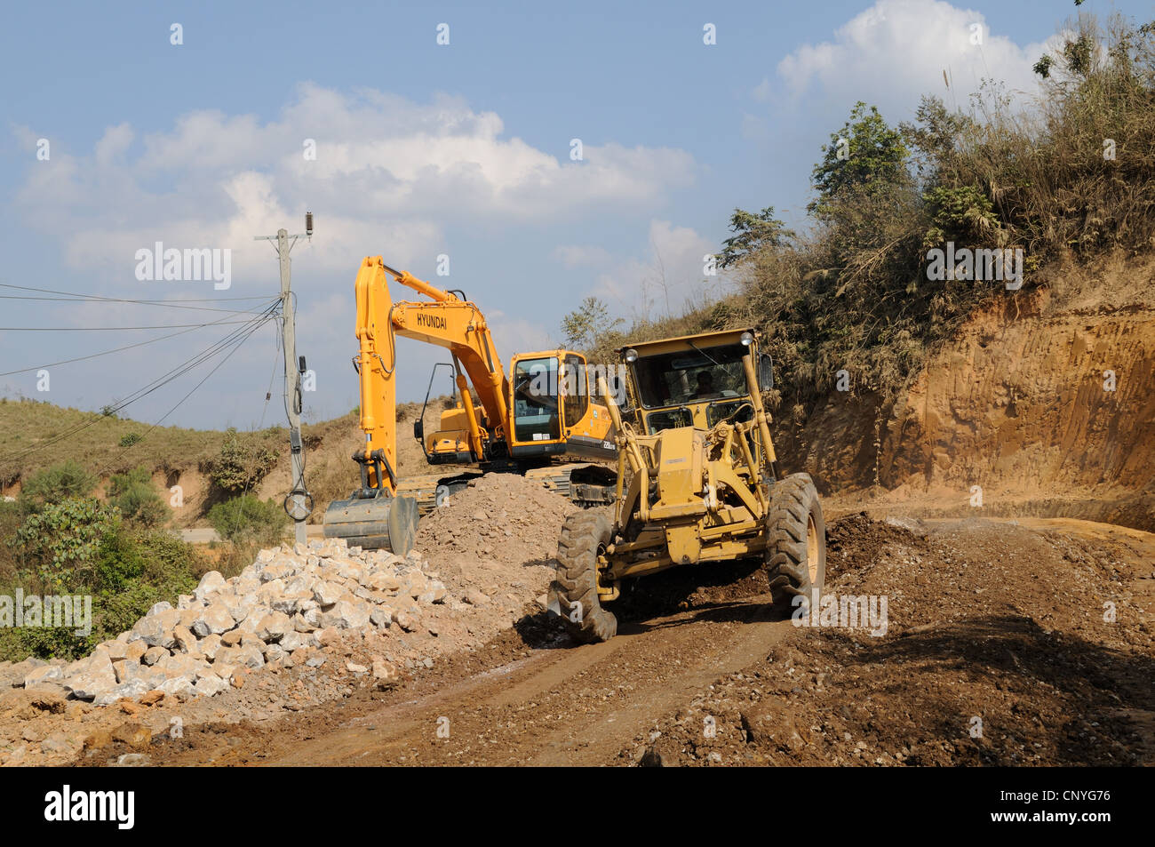 Laos landslide on a main road being repaired by machinery after a landslide caused during the rainy season - Stock Image