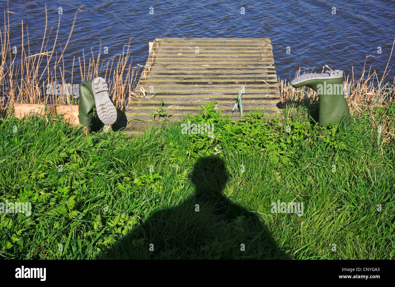 A pair of upturned water boots with a man's shadow on a river bank on the Norfolk Broads. - Stock Image