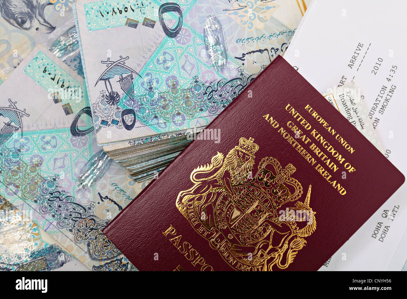 A new British passport with a booking form for a flight to Doha, Qatar, and a boarding pass on top of thousands Stock Photo