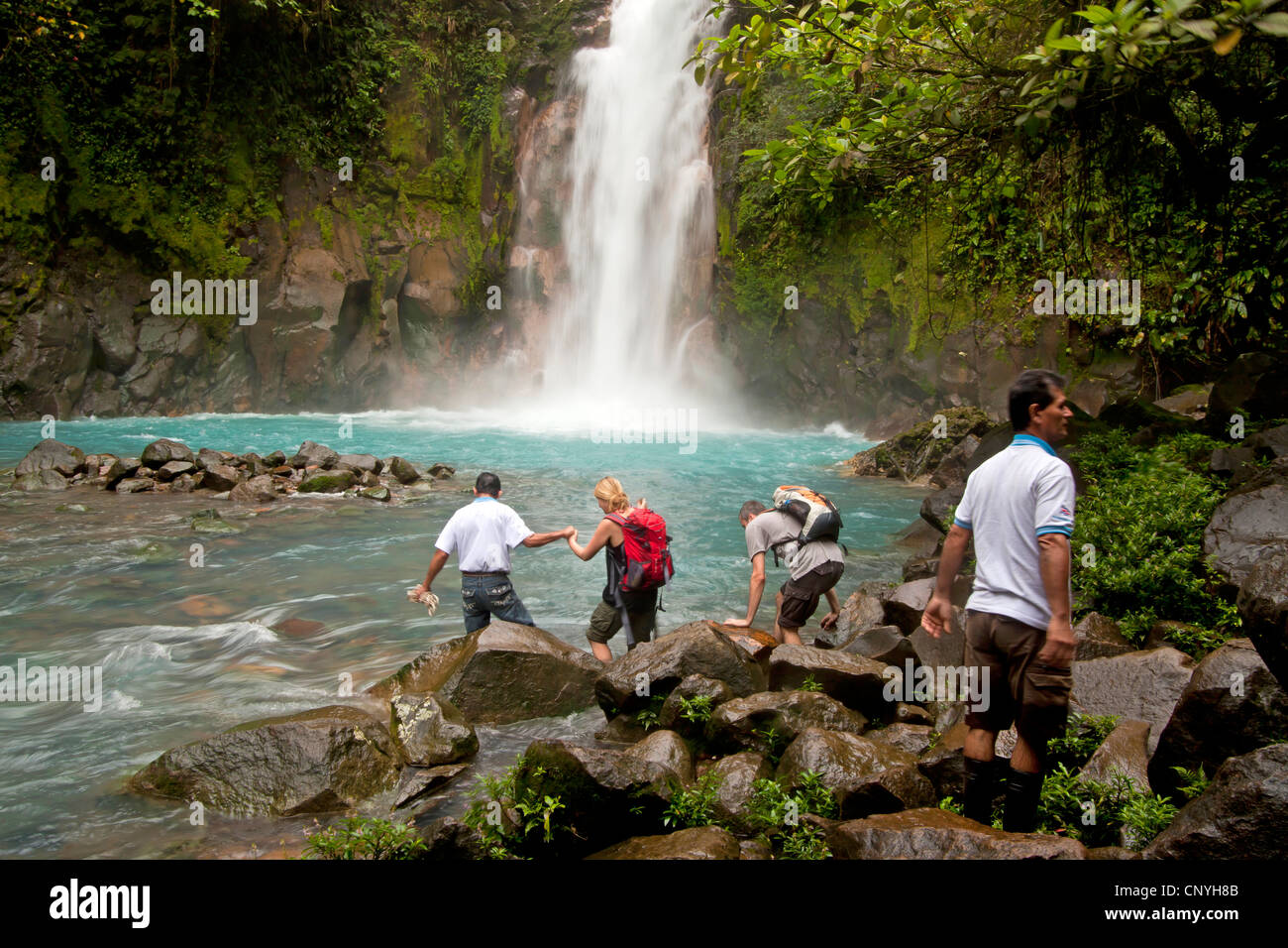 tourists at the Waterfall with the blue waters of the Rio Celeste in VolcanTenorio National Park, Costa Rica, Central - Stock Image