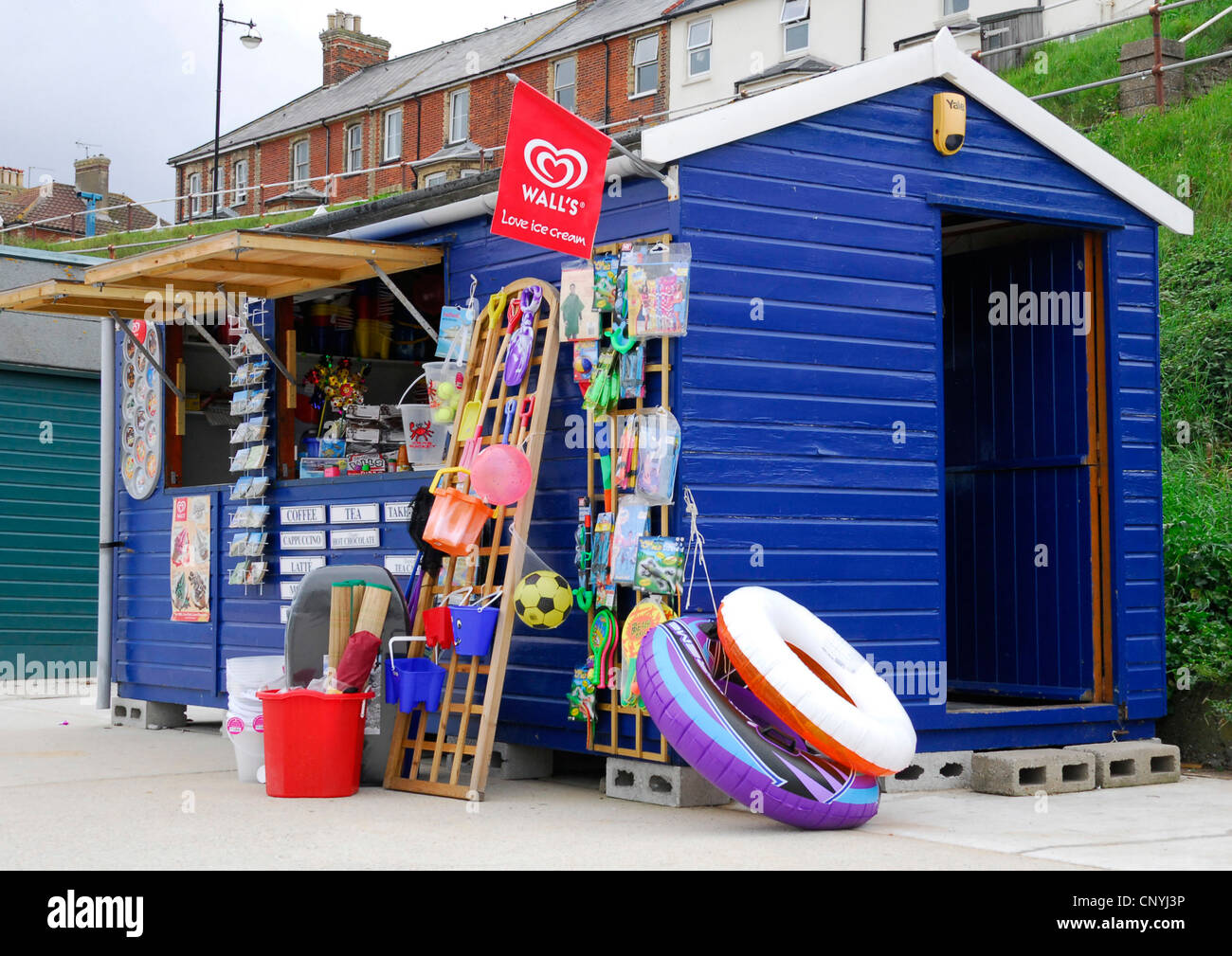 Suffolk - Southwold - seaside stall - colourful display of buckets - spades - postcards - swim floats -ice cream - Stock Image