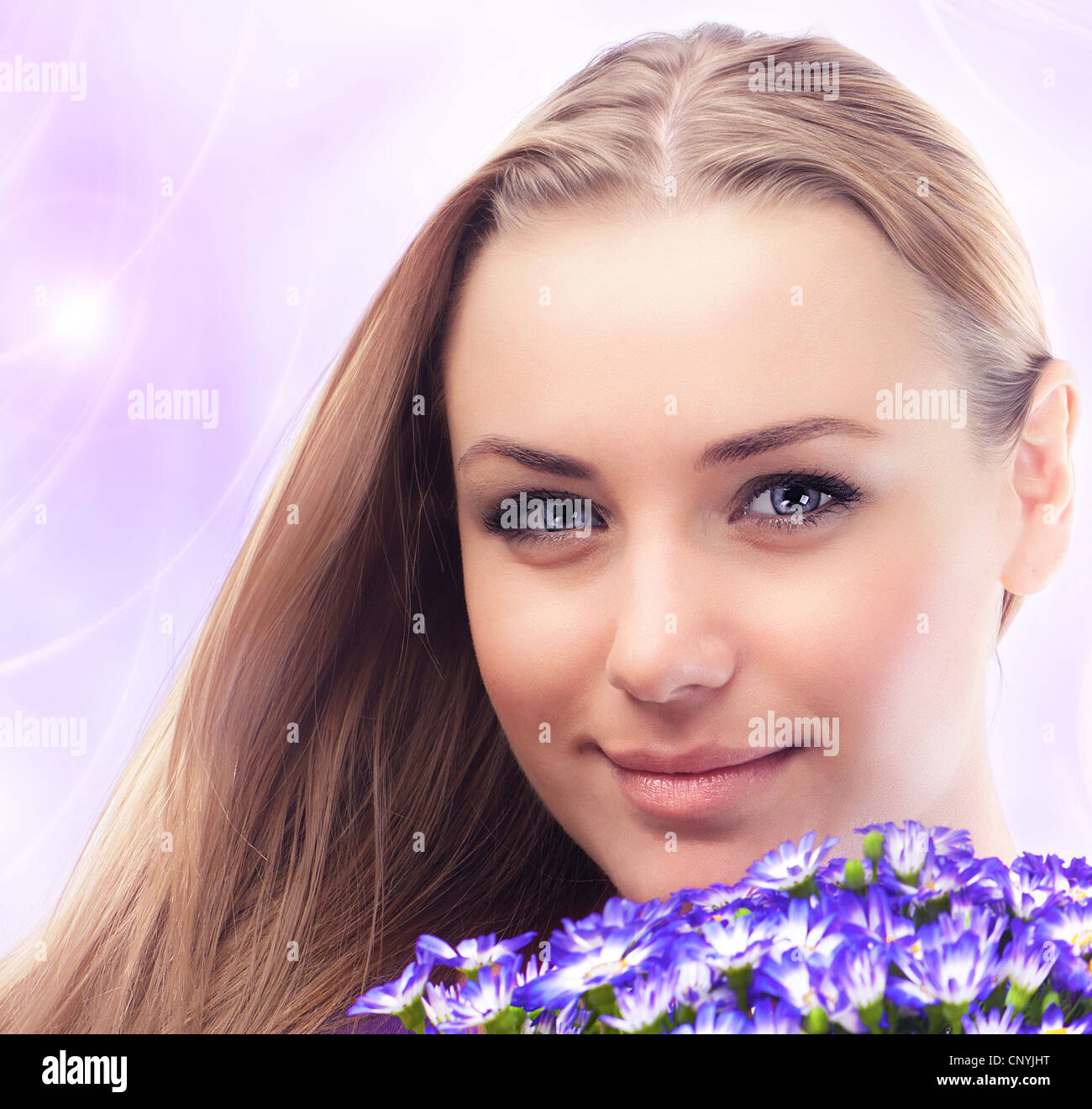 Girl face with bouquet of spring plant, bunch of purple cornflowers, lovely woman with gift over pink abstract background Stock Photo