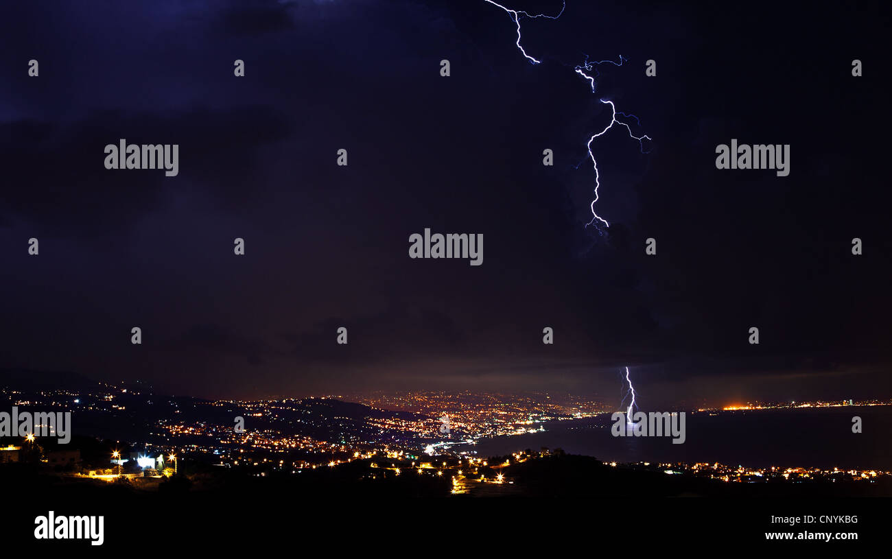 Lightning, thunderstorm at night sky, overcast winter weather with dramatic sky over city - Stock Image