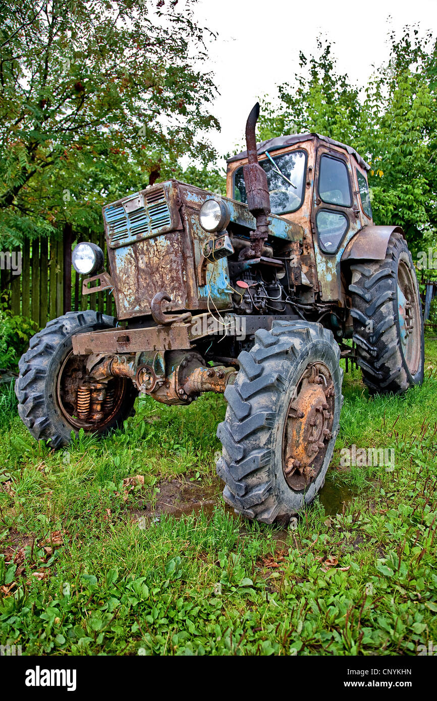 Old tractor against trees (HDRi) Stock Photo