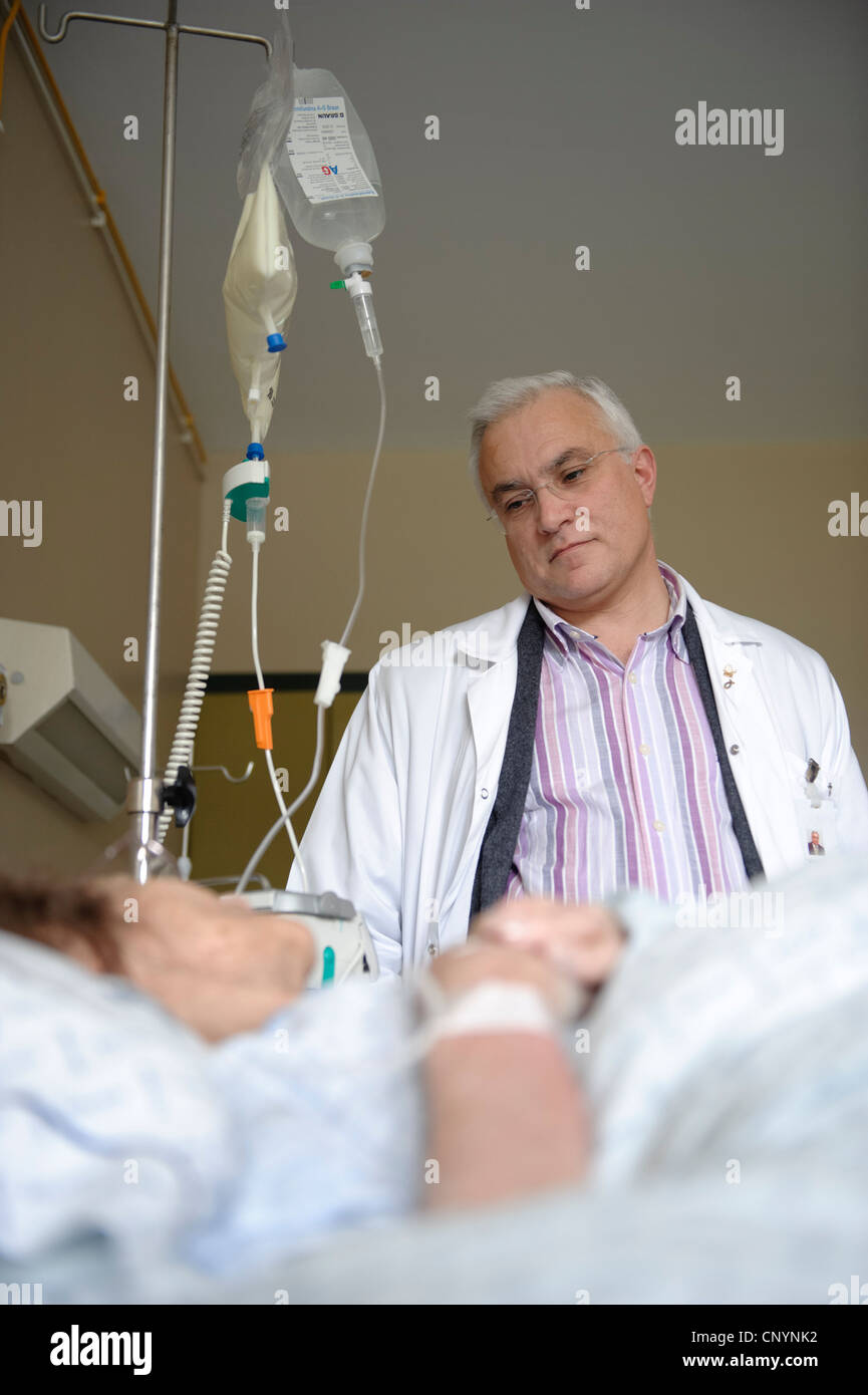 Doctor next to patient's bed in hospital ward - Stock Image