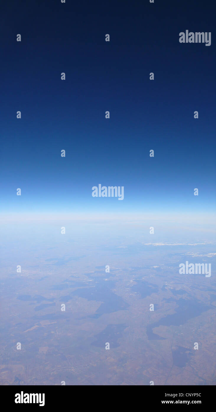 view out of plane window on a cloudless sky over a vast landscape - Stock Image