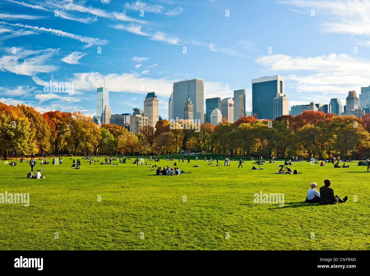 People relaxing in Central Park, New York City, in Autumn, looking towards the Central Park South skyline from Sheep - Stock Image