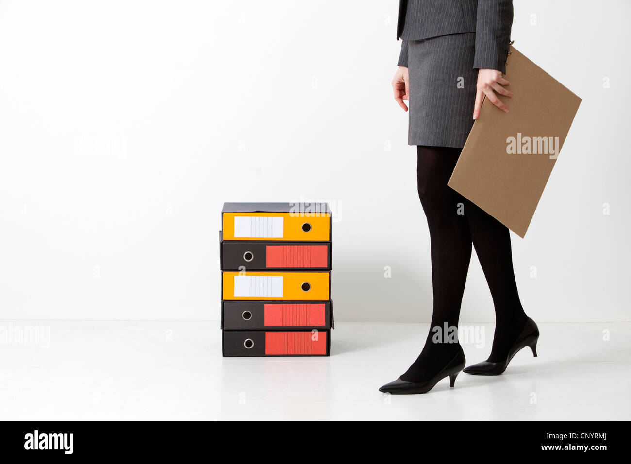 a woman with a clipboard and binders for documents - Stock Image