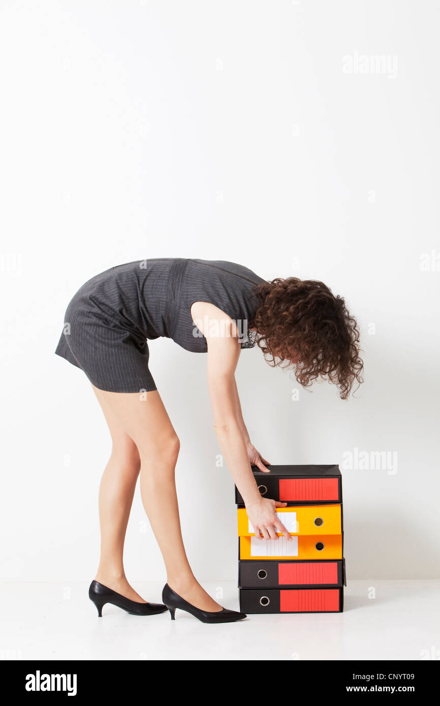 a woman while checking bins for documents - Stock Image