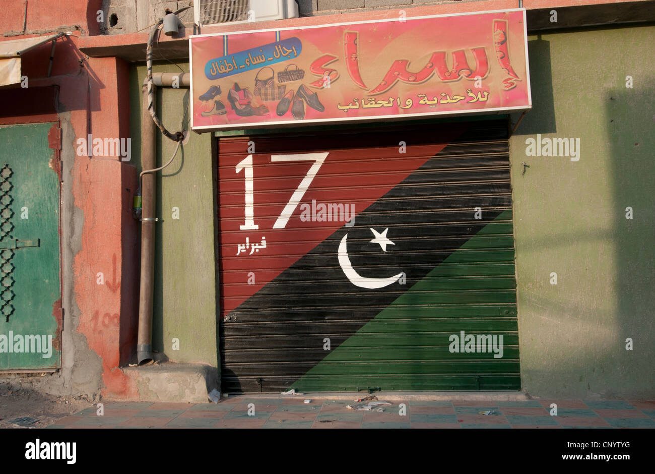 Nalut. The post Gaddafi Libyan flag is painted on the closed shutter of a shop, along with the date of February - Stock Image