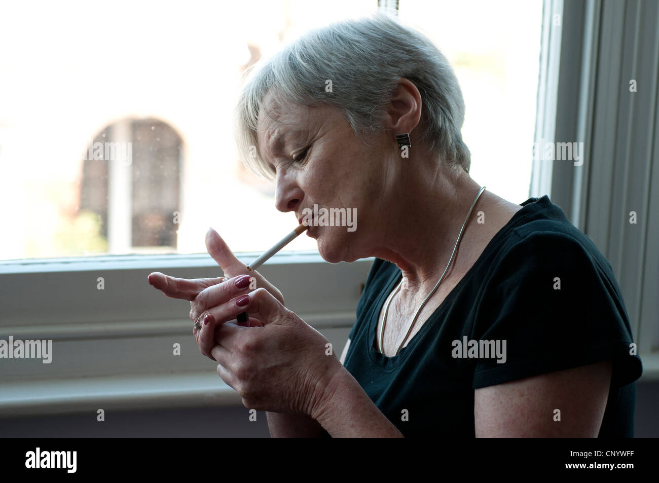 Middle aged woman near window lighting a cigarette - Stock Image