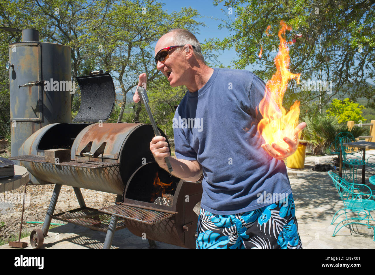 Backyard Bbq Composite Of Man In Shorts Playing With Fire