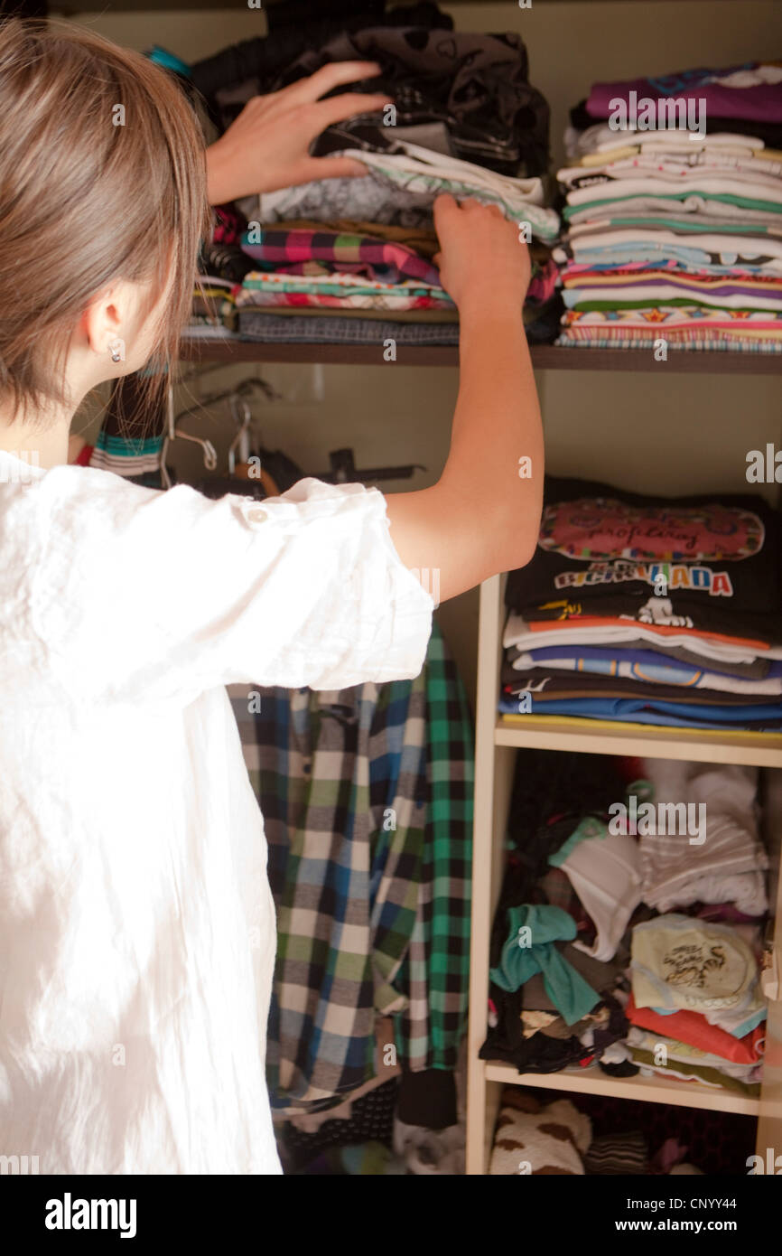 woman from behind while the system in a closet - Stock Image