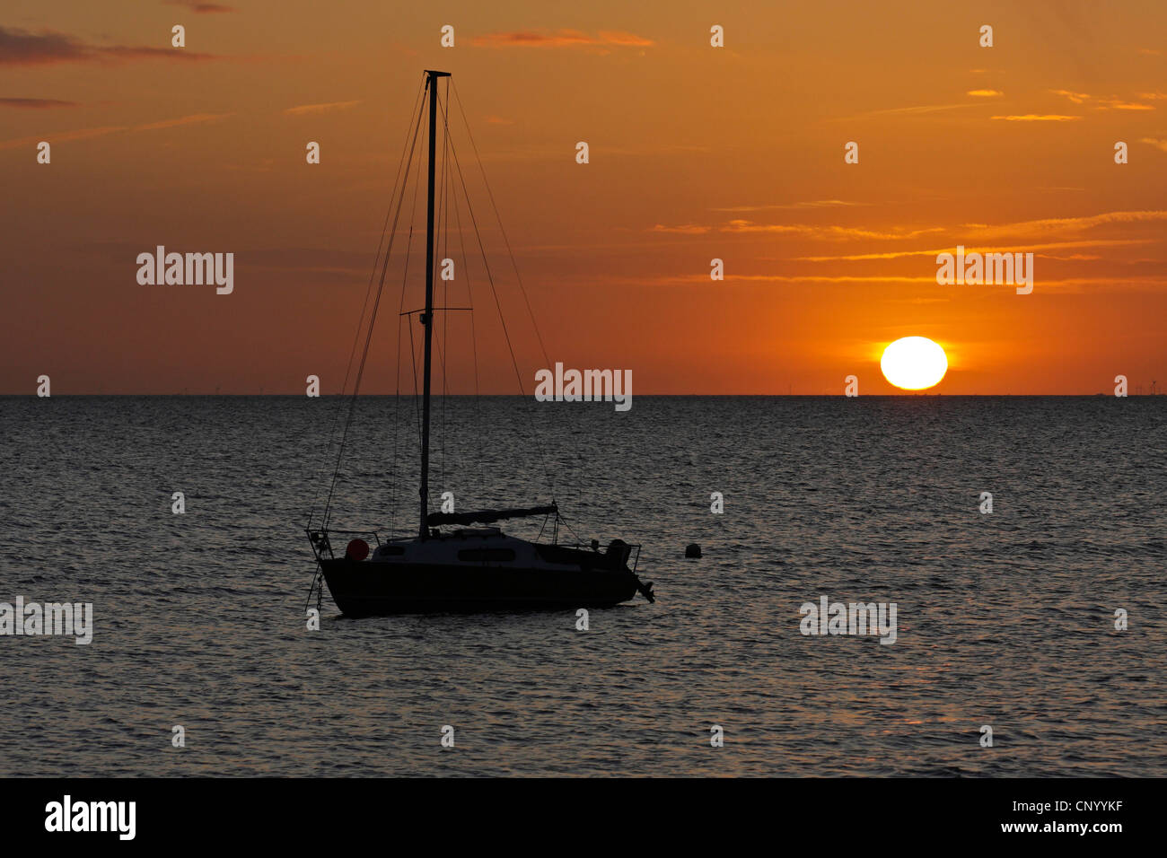 sailing boat on the sea in front of sunrise, Germany, Schleswig-Holstein, Sylt Stock Photo