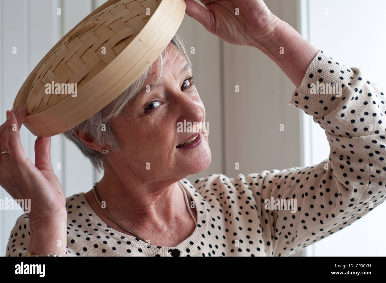 Middle aged woman playing with bamboo lid in kitchen - Stock Image
