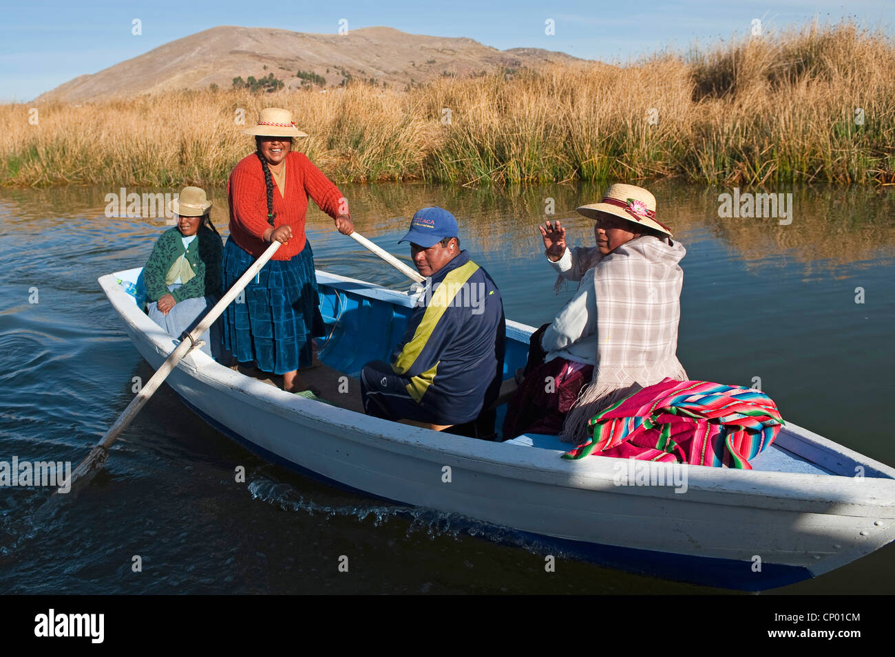 four Quechua or Uros Indians in a rowing boat on Lake Titicaca at one of 42  floating islands called 'Uros Islands', - Stock Image