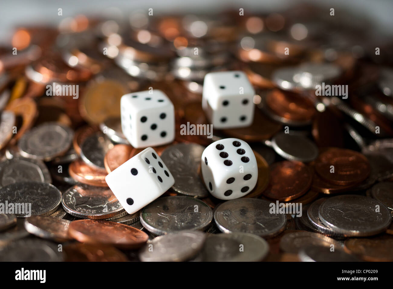 Dice on pile of coins - Stock Image