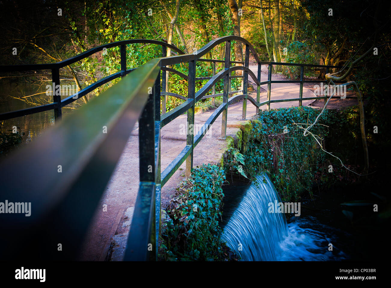Wishing Bridge with metal handrails over the weir between Lymm Upper and Middle Dams at Lymm Dam, Lymm, Cheshire, - Stock Image