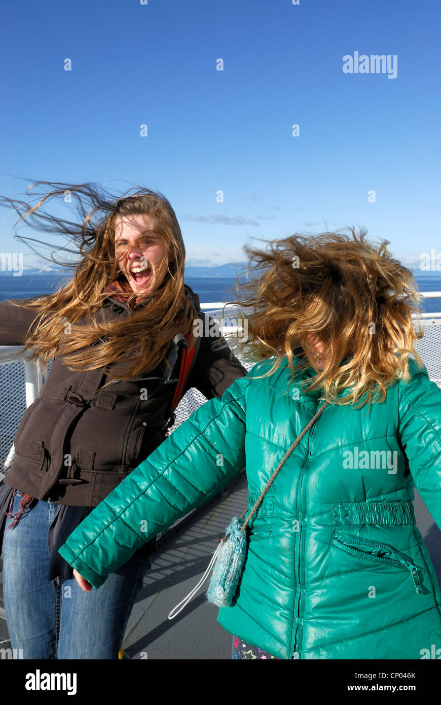 Two females with their hair being blown by the wind during a ferry ride. - Stock Image