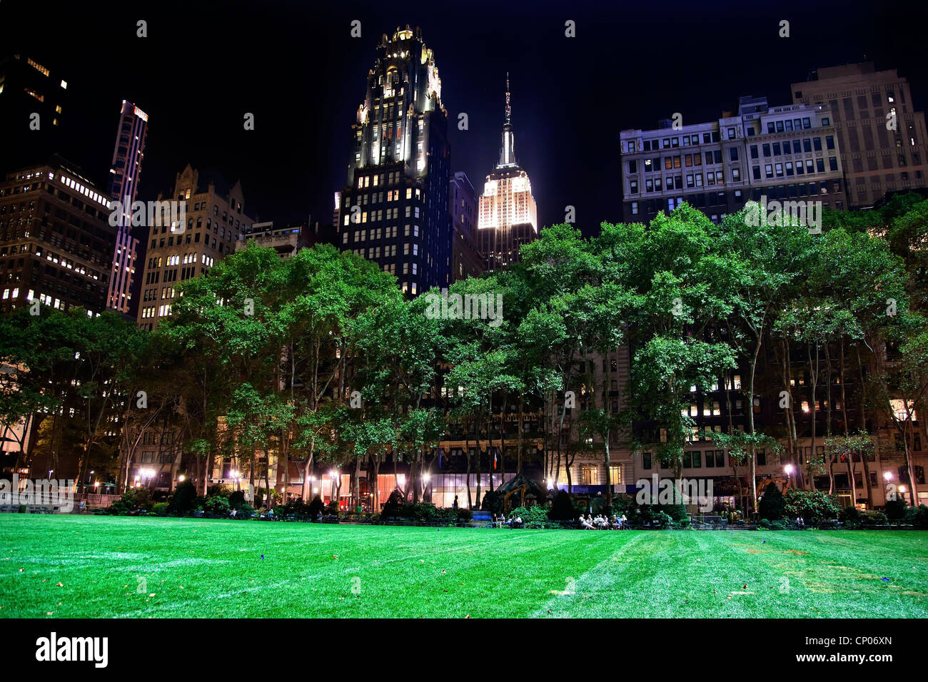 Bryant Park New York City Green Grass Skyline Apartment Buildings Empire State Building Night - Stock Image