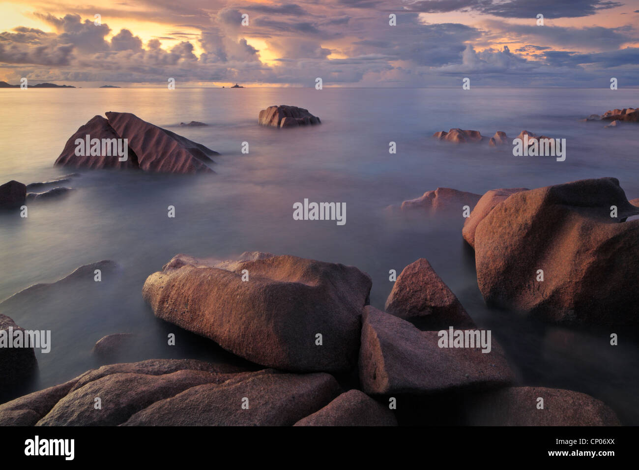 Storm clouds over the Baie Ste Anne at sunset as seen from the north end of La Digue in the Seychelles - Stock Image