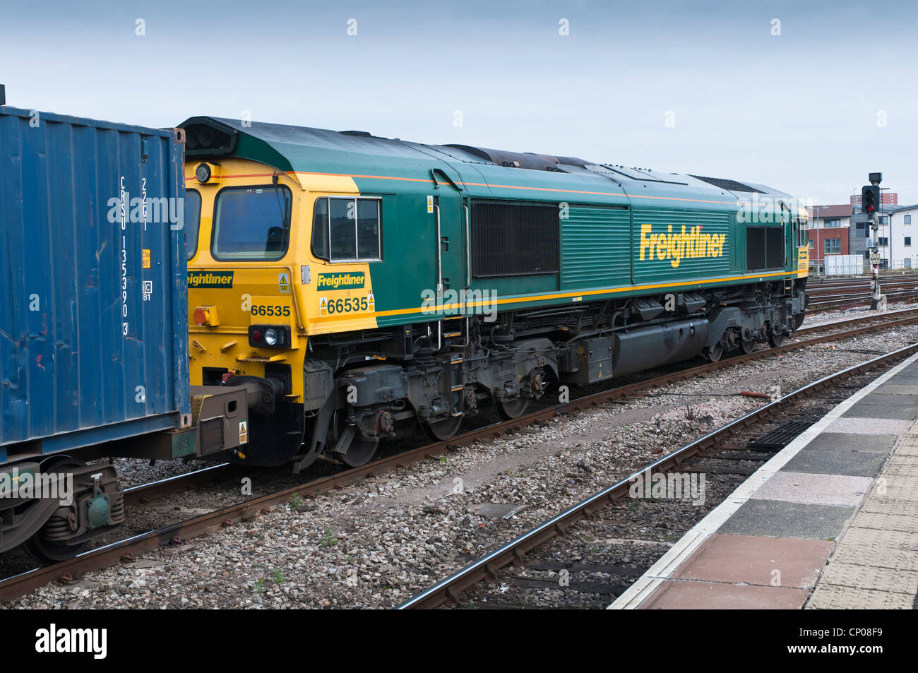 A  Freightliner Class 66 locomotive waiting at a red signal heading a train load of container freight wagons. - Stock Image